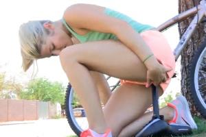 Mladá holka si strčí sedlo z kola do kundy na veřejnosti